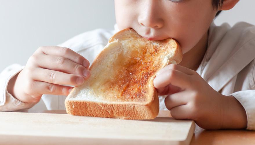 朝ごはんを食べる小学生